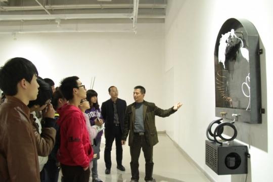 温州大学的学子们组团来接受艺术教育,美术馆工作人员在进行导览