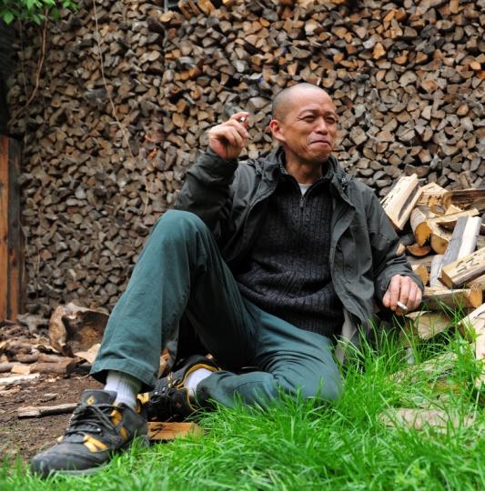 艺术家何云昌在作品《出入》前,他在闲暇的时候砍柴,并记录下时间