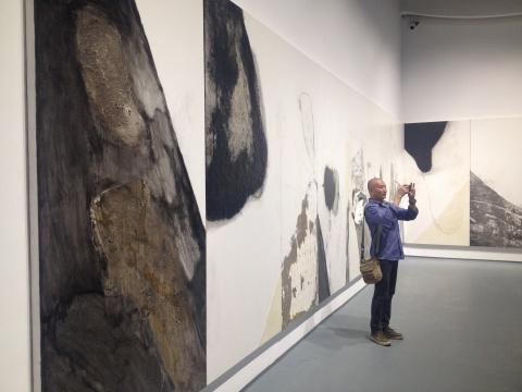 """乔晓光出现在了""""不朽的风景""""展览现场,背后为尚扬的作品《剩山图》"""