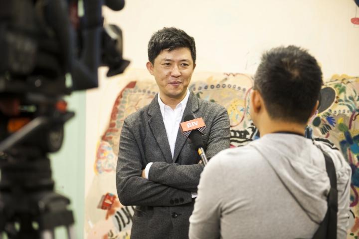 董梦阳在诚品画廊展位接受采访,这里有一张艺术家王玉平创作的《董梦阳》