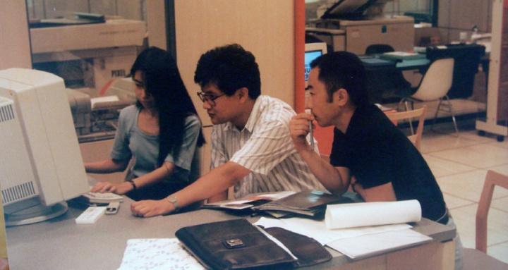 """1991年,""""新刻度小组""""作品《解析-1》参加日本福冈""""非常口""""的展览,图为王鲁炎在与技术人员于电脑上制作《解析1》 图片提供:王鲁炎"""