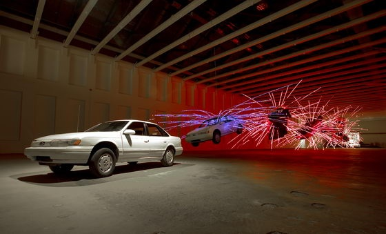 """作品""""舞台 No.1"""",来自2004年12月11日在美国马萨诸塞州当代美术馆开幕的个展""""不合时宜""""。  蔡国强使用九辆汽车创作了像一辆汽车在自杀爆炸中的翻滚定格过程"""