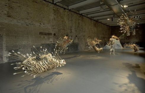 """作品""""舞台 No.2"""",来自2004年12月11日在美国马萨诸塞州当代美术馆开幕的个展""""不合时宜""""。  身上插满箭的九只仿真的老虎张嘴呲牙地悬在空中"""