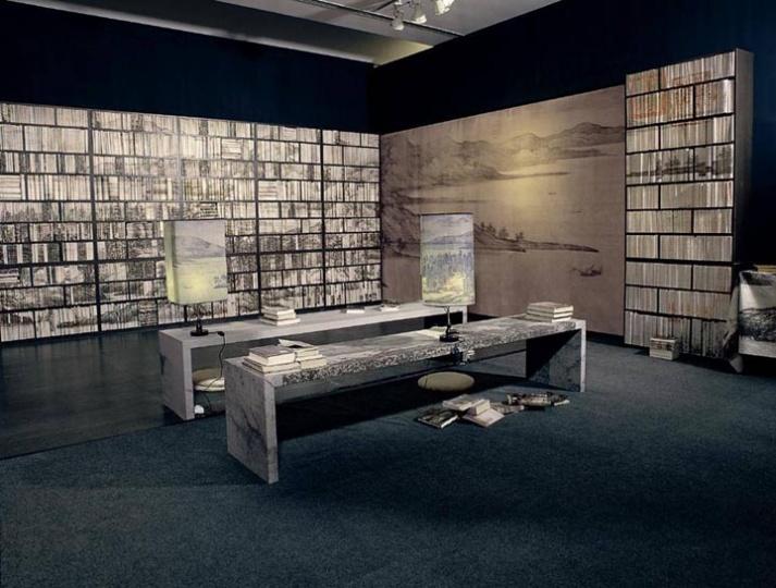 """2003年《山水书房》 装置,长9米 宽6米 高3米,参加第50届威尼斯双年展中国馆""""造境""""。房间被布置成水墨文化空间,制作的书架上是5000多册中外各类书籍,以书架的书脊将一幅五代董源的山水画《夏景山口待渡图》用电脑分割,再拼出整幅画面。山水画一定程度上代表了中国传统文化精髓,与观众、当下生活发生关联。"""