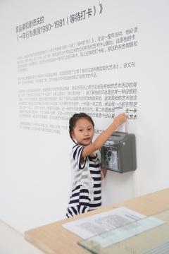 展览现场,袁运甫和谢徳庆的《一年行为表演1980-1981(等待打卡)》,一位小观众通过打卡记录自己到场时间。