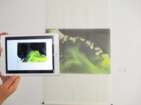 拿着平板电脑,打开特殊的App,对准墙上的平面作品《生》,意想不到的事情发生了。显示屏像被施了魔法,再现了图像背后的创作过程。