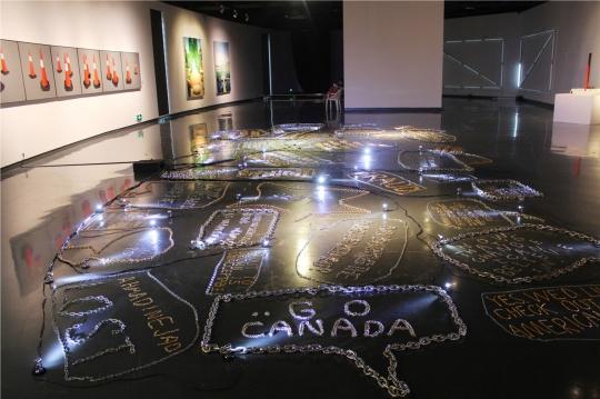 徐震2009年装置作品《金属的语言》,金银两色粗细不同的铁链在美术馆地下一层的地面圈画出时下流行语汇,每句话的呈现方式是手机对话框,其间穿插点缀着发光的白色小灯,它趴在那里,足够吸精,你会想去看每一句话的。