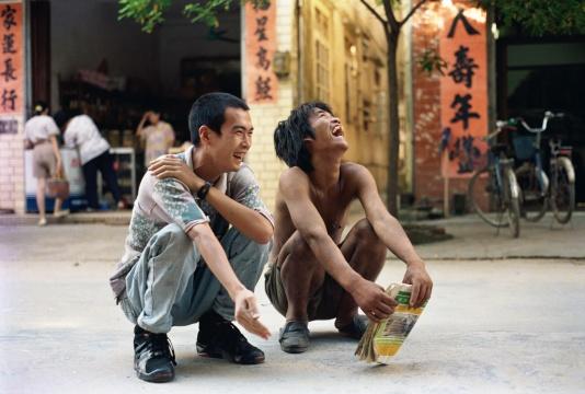 """《我和我的老师》郑国谷(1970-)摄影/录像/行为 182 × 270 cm 1993 年   1993年,23岁的郑国谷以《我和我的老师》彻底抛却过去,登上了他20余年如一日的年轻艺术之途,至今仍不见尽头。""""我的老师""""是郑国谷在家乡阳江街上偶然遇见的一位疯子,一无所有,却无比自由。郑国谷读到他不按常理出牌的衣食住行方式背后的颠覆性提问,他说自己虽然蹲下来和""""我的老师""""一起大笑,但还是""""没他放得开,略显拘谨""""。然而,非常规能量已经接续,郑国谷之后20年如一日的持续性""""无法不破,不立一法""""的艺术实践不断积淀着作品的厚度:他是最早一批进行实验摄影的艺术家之一,那些由傻瓜相机拍摄的《度蜜月》的作品被很多艺术家所深深铭记;2001年,他购买了七套顶层商品房,打通连接建成自己的家,在房地产市场崛起之前已经在发问;他推动成立的阳江组致力于对传统书法破绽的寻找,并关注到向来被忽视的底层书写;他按照先锋艺术家的生活方式将教学带到酒吧,给每位学生打99分;他建于郊区的3万平米个人当代艺术实验田则经历了从天马行空、漫无边界的""""帝国""""到""""了园""""的不同阶段,耗近十年之功而至今未了,土地制度、人权、资本、想象力、艺术的边界等等均搅和在一起……很少有艺术家像郑国谷那样将自己的生活和艺术的先锋实验像如此紧密而多样地交织在一起。这位受到多方重视的艺术家既是海内外的重要大展的常客,却又始终没有离开自己出生的小城阳江,吃酒喝茶关照家人,并把身边的生活重又变成艺术。"""