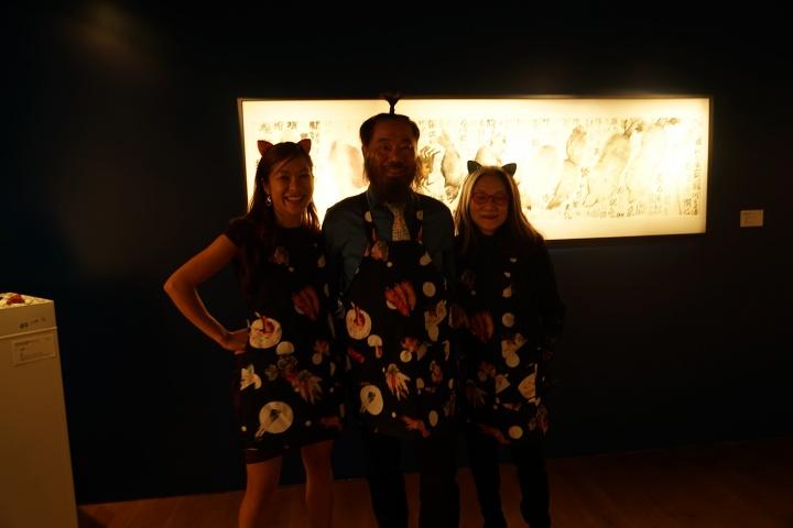 苏富比香港新水墨部主管唐凯琳、艺术家李津和苏富比顾问龙美仙身穿特制的围裙在作品前合影