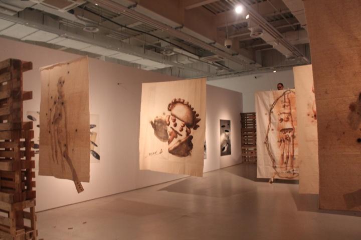 """艾德加•阿斯诺混合媒材装置《运算不爱你:从底特律到上海》中的一部分——《《底特律众神》,作品以黏土、木炭和珐琅制成,人物怪异,画面下方是刻意拼写错误的城市基石性机构,它们是文明之""""神""""。"""