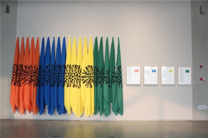 艺术与语言1978年作品混合媒材装置《组织的旗帜》,四张海报及四面旗帜,上面都有同样的黑色徽章,实质为某种虚构组织。