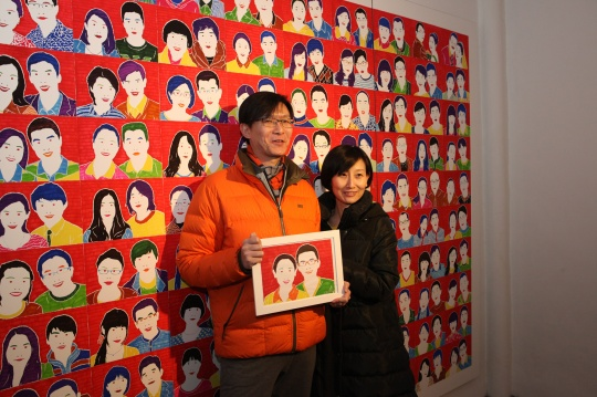 领取版画后的夫妻在《百婚图》前