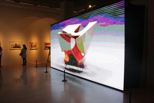 展厅中大型的电子屏幕持续播放四位艺术家的纪录片