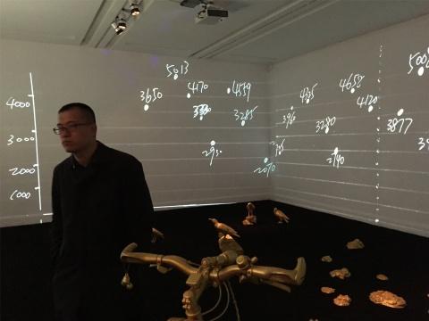 张宁在现场,背后是装置(乌鸦及牛粪)、影像(骑行中的海拔数字及沿途风景)