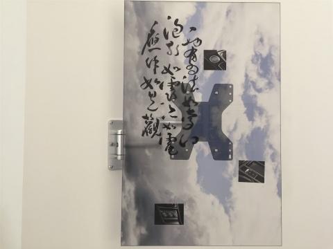 贾小丁作品《虚空间隙》,以钢铁固定在墙面的装置作品,这一件画面上的书法为《心经》,汽车元素,另一件的画面是多芬香皂的借用