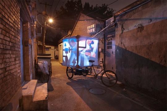 """艺术家尼克·德·拉法耶(Niko de La Faye)带着一个安置在中国传统三轮车上的宇宙乾坤的象征物(八卦车)从北京到上海、再到香港,并在香港艺术博览会上举办了""""M2B北京——香港""""展览。图为《M2B》影像记录截图"""