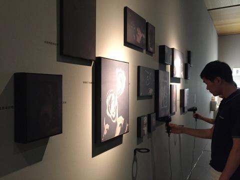 观众在设计学院作品前与展品互动