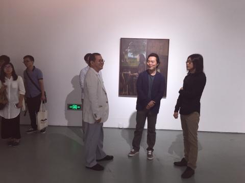 艺术家魏东(中)、策展人朱朱(右)向今典集团董事长、今日美术馆创始人张宝全介绍展览