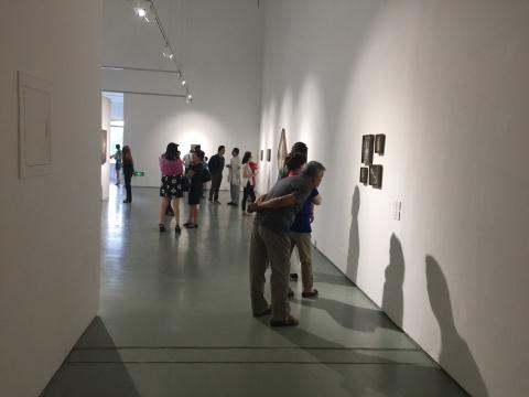 展览现场仔细观察作品的观众