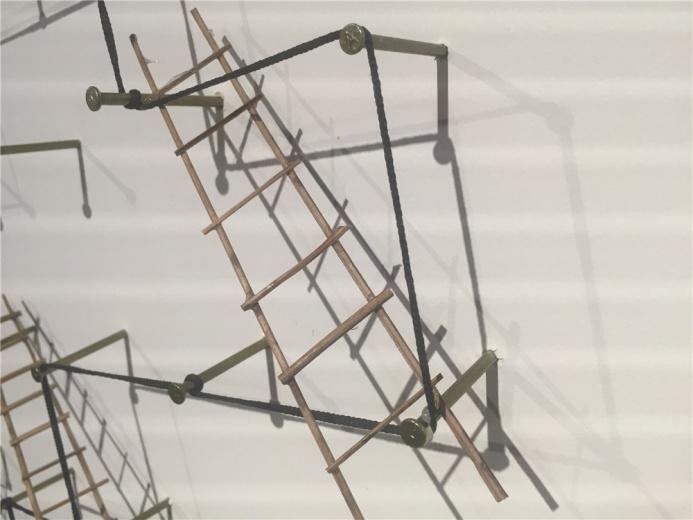 伊拉克艺术家瓦利德.西蒂 2014年材料作品《攀爬的分解》,作品局部中铁钉、木质小梯、黑色线绳的交织组合在墙面投影构成作品的虚部空间