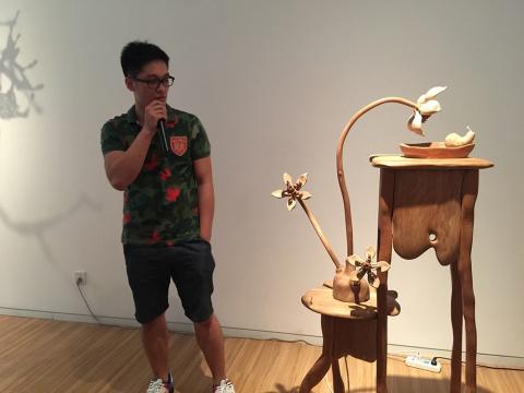 艺术家李庆阳为现场观众及媒体解读自己的作品  右 《黄昏》 155× 80× 45cm   红樱桃木、电视机等  2014