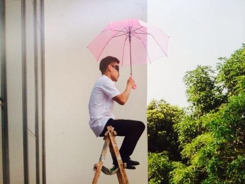 """《看风景》广州市越秀区二沙岛 2014年6月14,展览的邀请方请他做现场的行为,他以拒绝表演的态度,在开幕的时间内,于展厅外的阳台上坐了两个小时,带着眼罩打着伞,曰""""看风景""""。"""