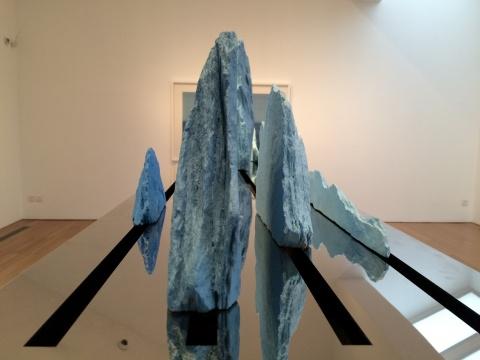 透过底座的镜面不锈钢,山石如水面一般透出它的倒影
