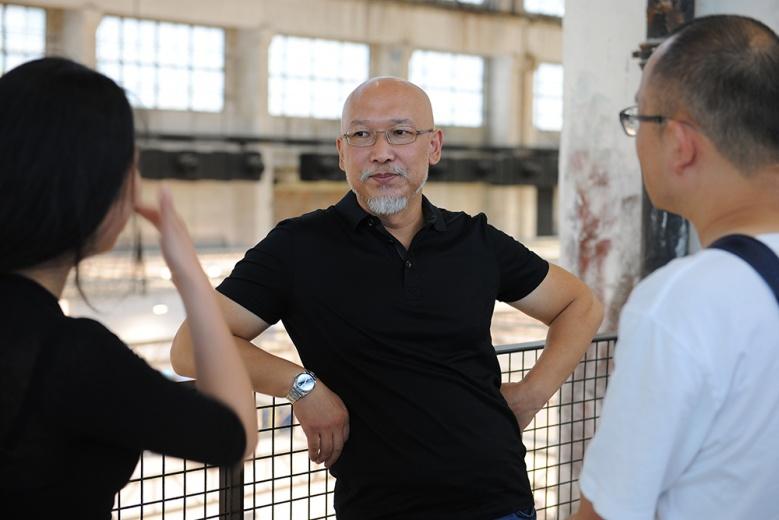 艺术家张恩利在现场与身边的朋友交谈,整个人非常地轻松自在。