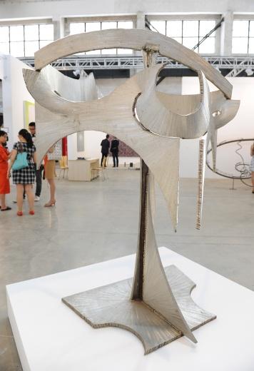 """马克·迪·苏沃尔(Mark Di Suvero)在创作时不打草稿,把硬的材料做的柔软,可以动,可以摸。小件的雕塑也会使用钛作为材料。他被称为""""柔软的钢铁家""""。现场这件大雕塑《不速之客》(2002年创作)的售价在55万美金。"""