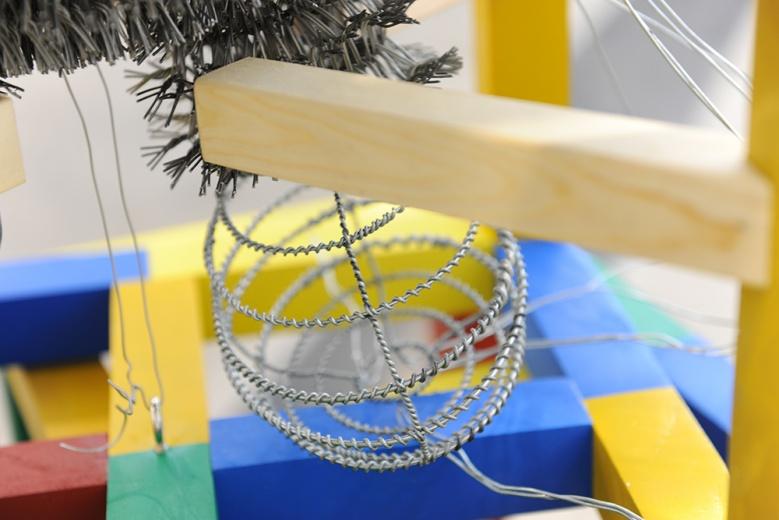"""周洁最新创作的《万无一失》,将充满""""荆棘""""的铁丝套在色彩斑斓的玩具框之中,一场成人的理想世界就此展开。"""