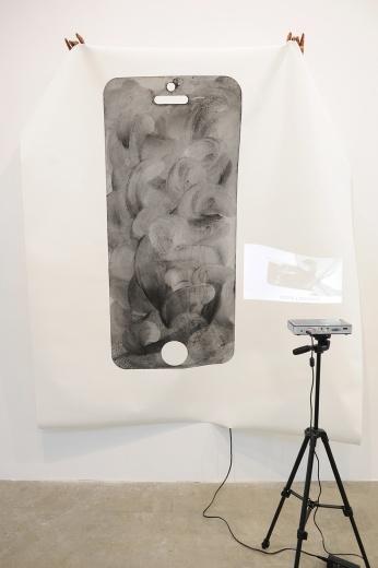 """天线空间带来李明2015年的作品《如何制造""""图像:i am"""",视频教程》,他用录像演绎手机上布满指纹却极具美感的图像是如何被""""创作""""出来的,延续了他在作品中一直都有的一种将录像物质化的倾向。基于手机在生活中的普及,艺术家甚至想要当一个""""录像教练""""。此件作品现定价为7万元人民币。"""