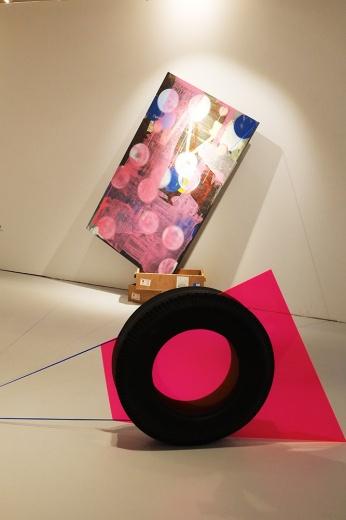 "Between艺术实验室以展览的方式,大胆在""艺术都市""上为数不多的装置类作品。因为预想和实际空间的差距,工作人员在呈现上做了很大的调整。刘健的作品《旅行》因为颜色和空间结构极为亮眼,作品在灯光的照射下拥有了线的阴影,视觉感强烈。垫在绘画下方的木箱是艺术家孙闻冠作品《无题》装运水泥砖头的箱子,这个箱子漂洋过海过许多城市,上面还留有运输过程中贴上的标签,这意外的添加正应了《旅行》的主题。"