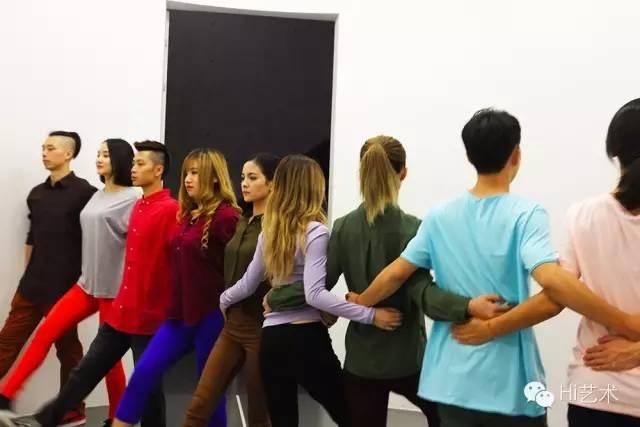 """阿洛拉和卡尔萨迪利亚《旋转门》 2011 一群舞者从墙的一端到另一端一字排开,阻挡观众的去路。他们的动作让人想到游行、部队行军和群舞表演。由舞者组成的""""人墙""""会慢慢旋转,迫使观众从房间的一侧移动到另一侧,就好像穿过一道旋转门。"""