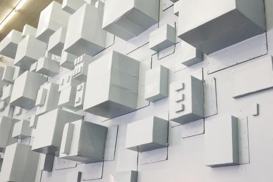 用粉刷后的纸盒子堆砌而成的墙面,凹凸不平的呈现在大家面前