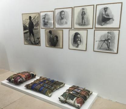包晓伟创做的当地难民素描肖像与油画(在本次展览中,绘画与作品并不是最重要的内容,它只是在这个过程里做过的一件事情。于是在艺术家与策展人的商量下,将10米长的油画捆绑起来,它看起来甚至有点像炸药包的形式。)