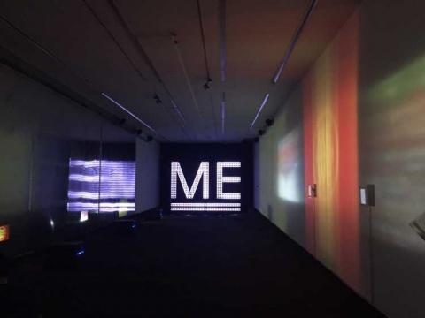 铺满柏油的长廊,两侧的墙上分别有不同的视频投影
