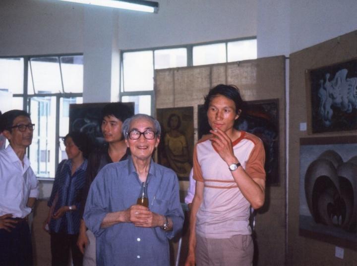 """1985年6月,首届""""新具像画展""""现场,毛旭辉与前辈关良先生在展厅合影。背景是毛旭辉作品"""