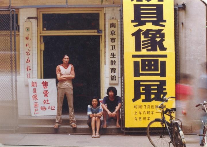 """1985年7月,首届""""新具像画展""""南京巡回展,展览地点位于南京市卫生教育馆,毛旭辉(左)、侯文怡(中)和潘德海(右)在展厅入口处留影"""
