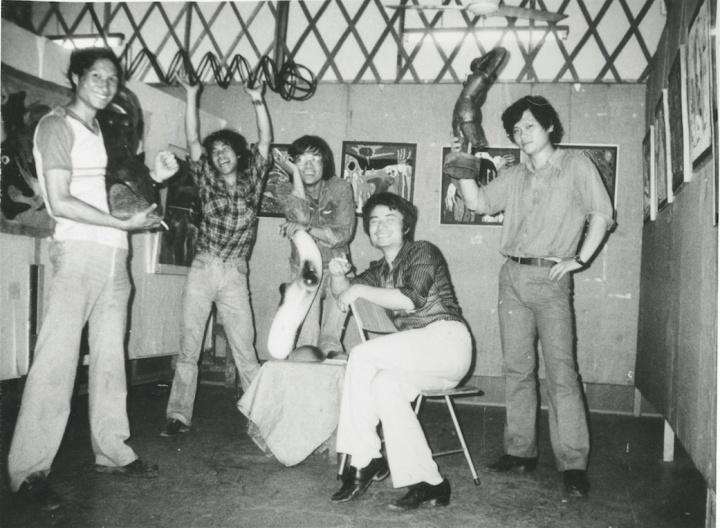 """1985年6月, 首届""""新具像画展""""在上海静安区文化馆举办,参展艺术家展场留影。左起依次为:毛旭辉、潘德海、张隆、徐侃、刘铁君。背景是张隆的作品,潘德海和刘铁君手中举的是徐侃的雕塑"""