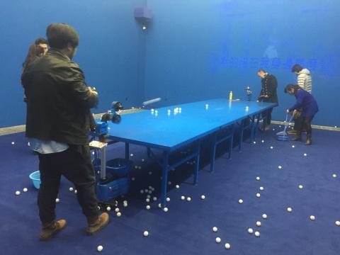 展厅内设置了乒乓球发球器,背景是夜间卡拉OK的投影