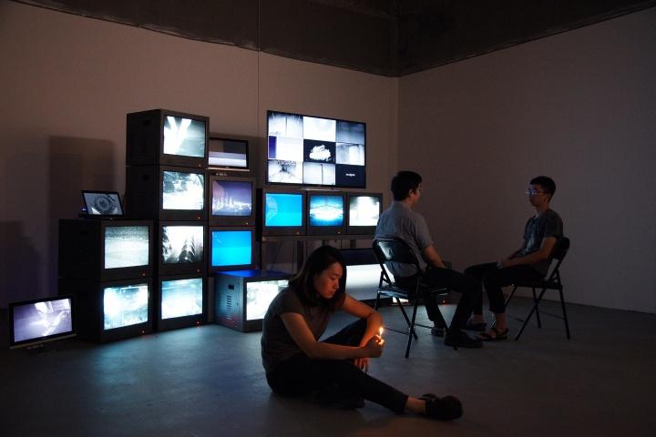 """获得""""评委会大奖""""的艺术家杨健作品《世界监控器——末日已经开始,只是没有坏事发生》,这是一出剧场表演,作为背景的电视墙上监视器播放着来自世界各地的监视视频,两位在监控室内工作的保安关于末日的对话以及一位不时介入的陌生路人的荒唐表演。摄影:萧潇"""