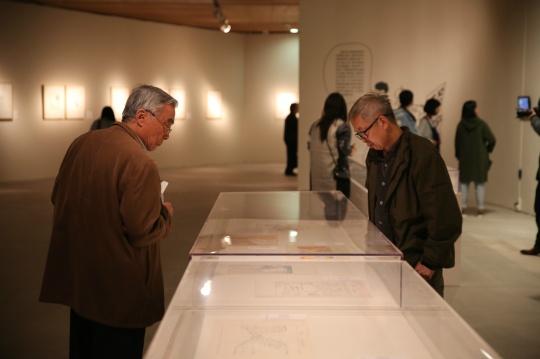 展览现场 观众在欣赏展柜里的漫画手稿