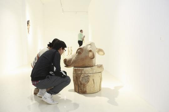 观众在展览现场刘恺作品前仔细品味