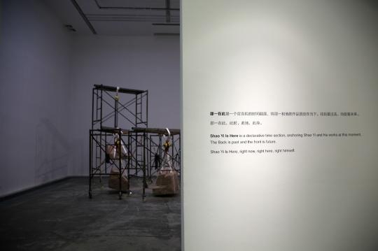 """站墙上文字写道:""""邵一在此""""是一个宣言似的时间截面,将邵一和他的作品固定在当下。往后是过去,向前是未来。"""