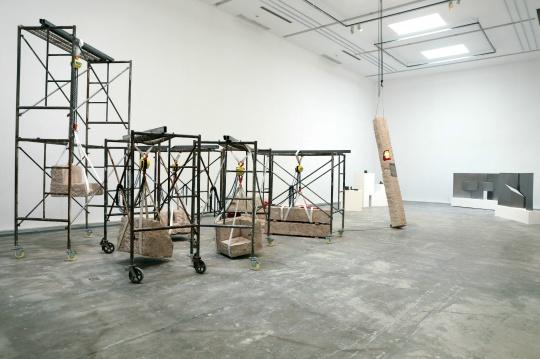 近景脚手架上悬挂着凝灰岩 是装置《合格品》系列 中间的石柱是《亮灯工程》系列的一件作品