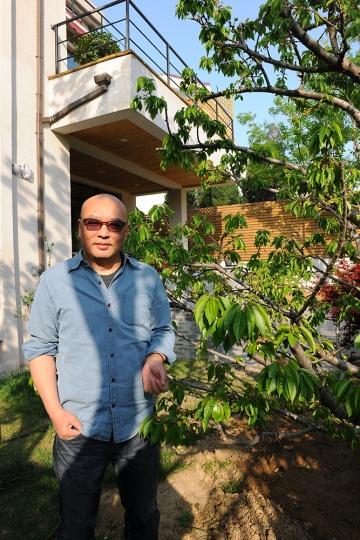 张晓刚在新工作室外的樱桃树下