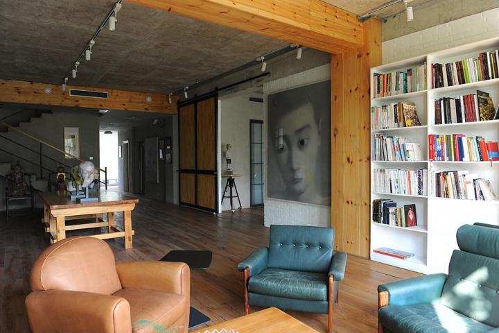 天花板和墙面是裸露的水泥和砖,门前墙上悬挂着张晓刚的作品,但对于工作室而言,除了作品我们似乎也应该关注墙面本身