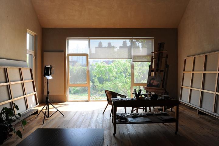 从二楼工作室看窗外的城市,工作室紧挨一条小河,河两岸种植的树木郁郁葱葱