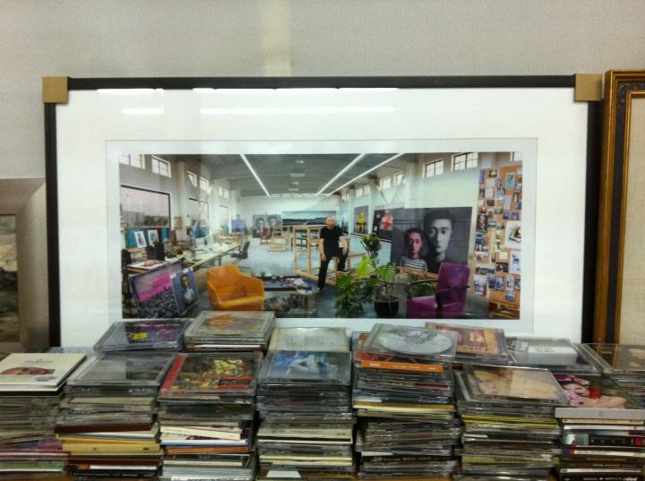 同一张照片。这张照片是在张晓刚旧工作室拍摄的旧工作室,是2014年拍摄的2008年。照片前面都是张晓刚收集的音乐CD,他喜欢的的音乐风格包括古典,现代,流行、摇滚等,最欣赏平克·弗洛伊德。