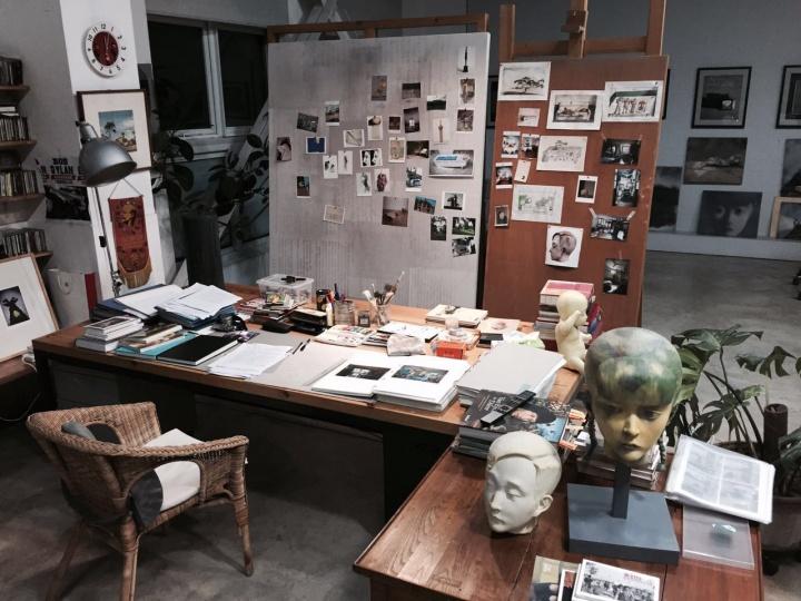 """这是张晓刚画小稿的""""书房"""",可以随时在这个大桌子上写写画画。后面贴了很多照片,这些都是张晓刚喜欢的照片、图片,随手贴在木板上,有时候可以当做素材和灵感的源泉"""